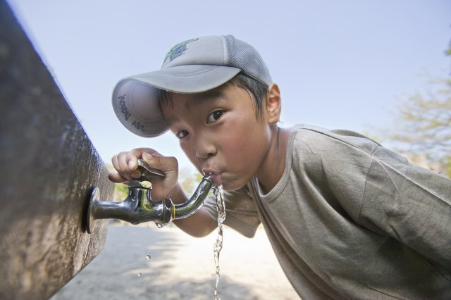 Boy drinking water from faucet, Japan