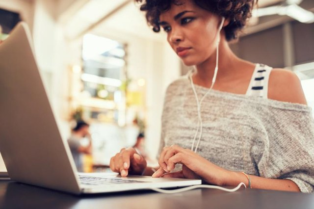 Portrait of young woman looking busy working on laptop at a cafe. African woman sitting in coffee shop using laptop.