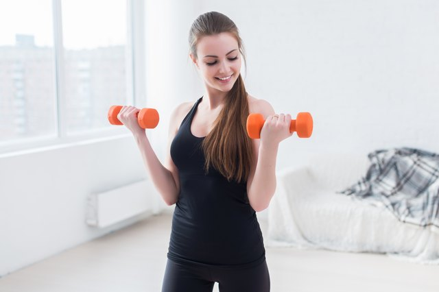 Active sportive athletic woman with dumbbells pumping up muscles biceps
