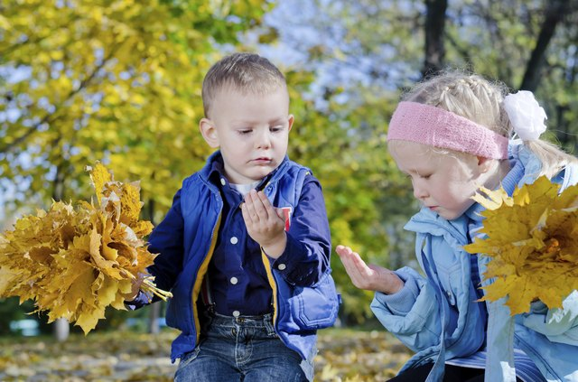 Boy and Girl Holding Autumn Leaves