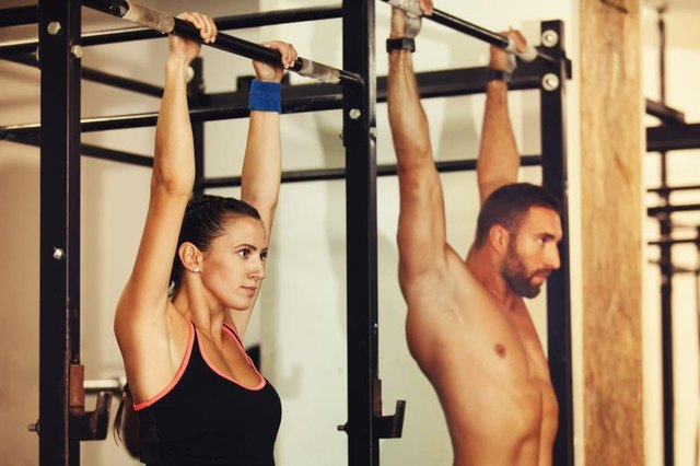 A man and woman about to do pull ups.