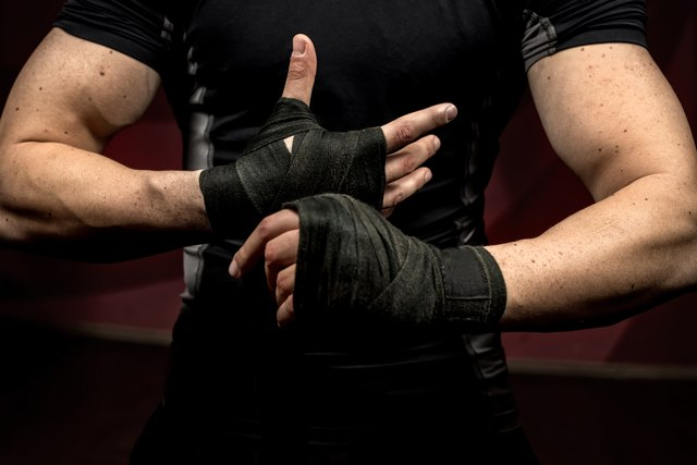 professional fighter preparing for training, wraping his hands and wrists