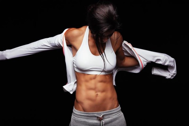 Image of muscular young woman wearing sports jacket. Getting ready for workout on black background