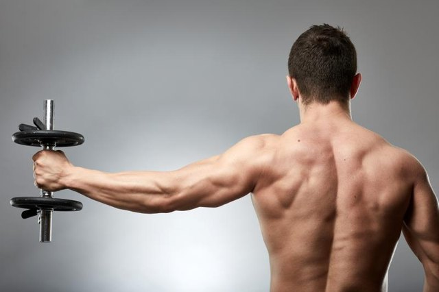 Man doing shoulder workout with dumbbell on gray background