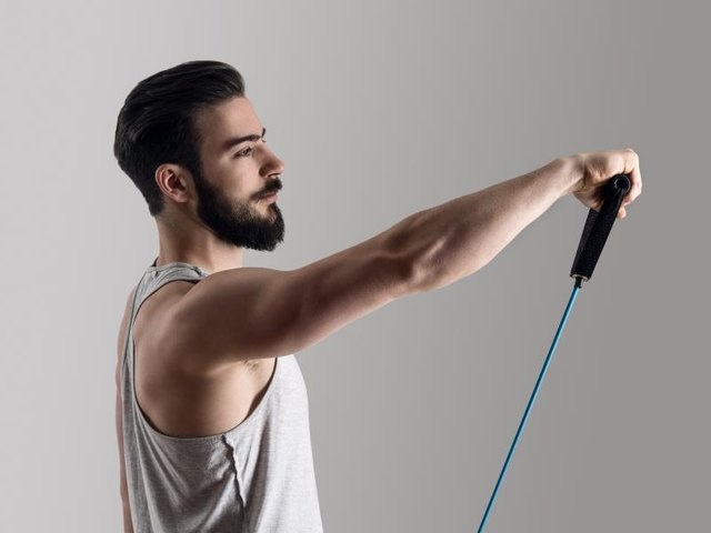 Side view of young athlete in tank top workout with elastic resistance band doing shoulder exercises.