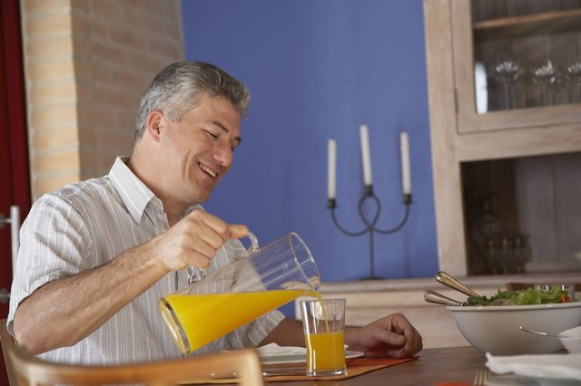 Mature man pouring juice at dinner table, side view