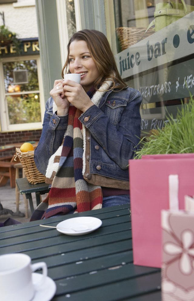 Young woman sitting outside cafe drinking coffee