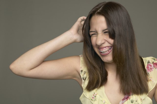 Young woman scratching her head and laughing