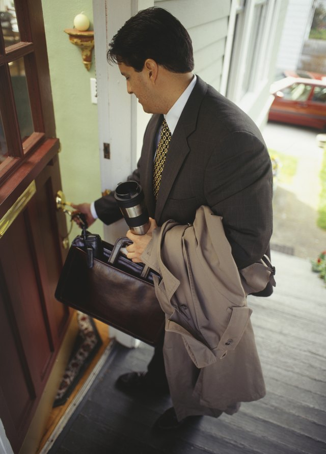 Businessman opening front door to house