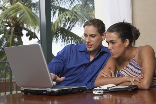 Mid adult man and a young woman sitting in front of a laptop