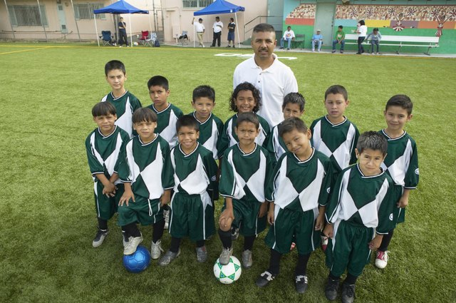 Portrait of boys (7-11) football team with coach