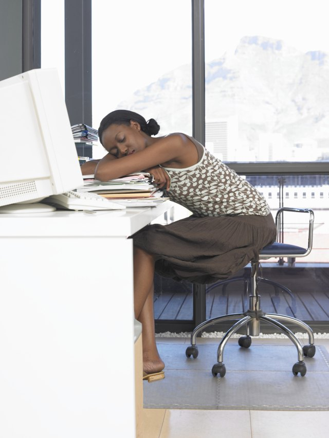 Young woman leaning on pile of files on desk, sleeping