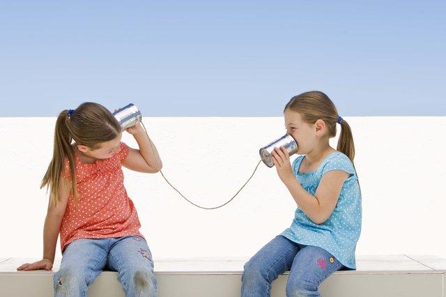 Twin girls with tin can telephone
