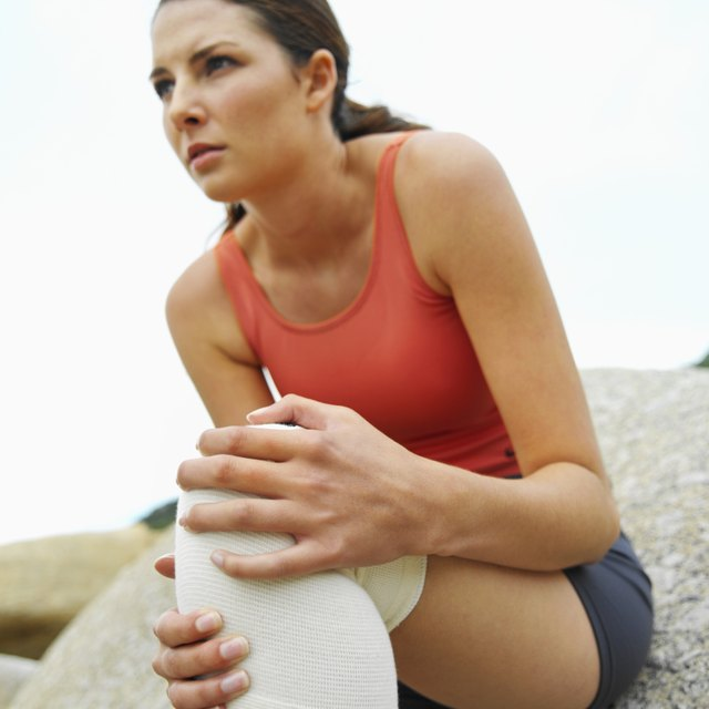 Low angle view of a grimacing woman wearing a knee support and holding her injured knee