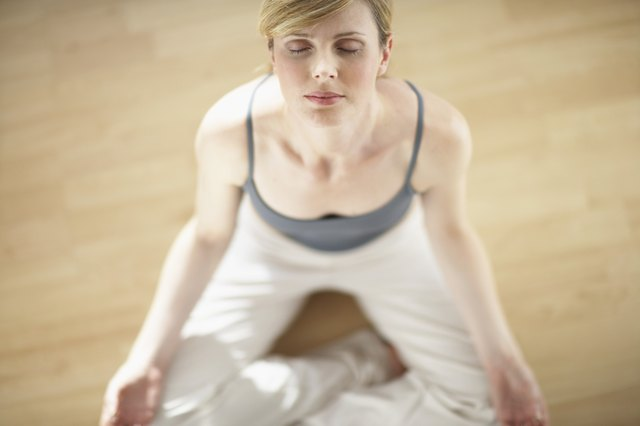 Woman sitting in padmasana position, eyes closed, elevated view