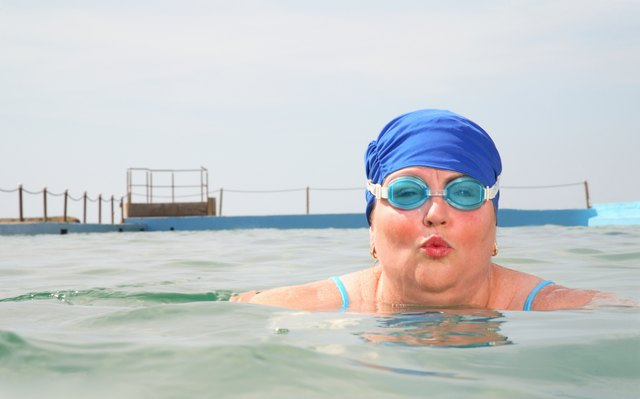 Portrait of mature woman swimming in pool, blowing kiss