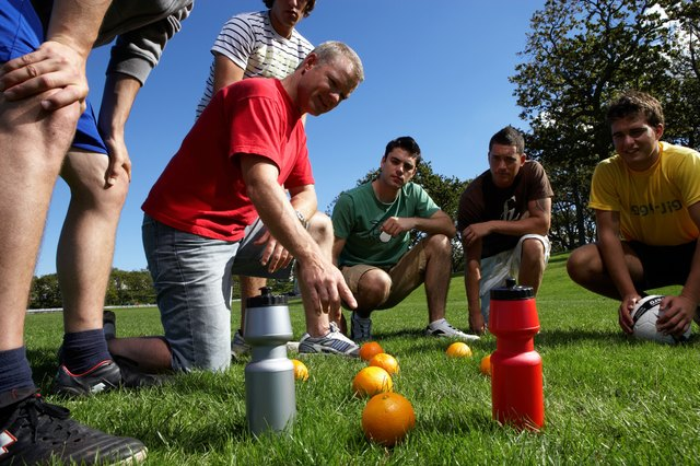 Group of men in park, planning football game by putting oranges on grass