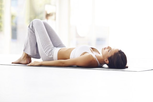 Exercising - Young fitness woman lying on a yoga mat