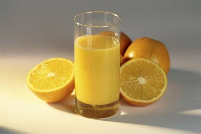 Glass of orange juice and oranges