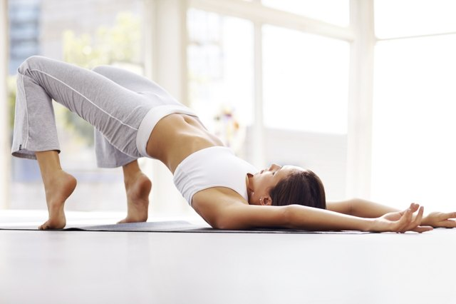 Young woman practising yoga on mat