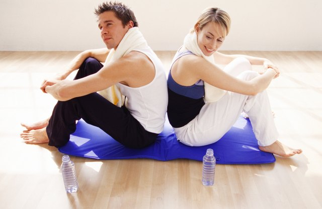 a young couple sitting back to back on a exercise mat