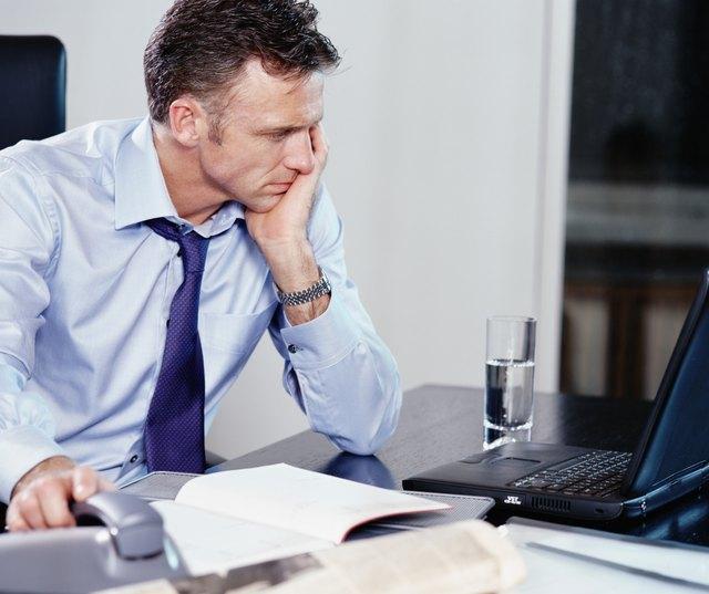 Businessman using laptop at desk, resting hand on phone