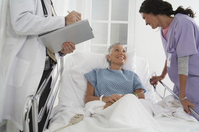 Patient in hospital bed speaking to Doctor and Nurse