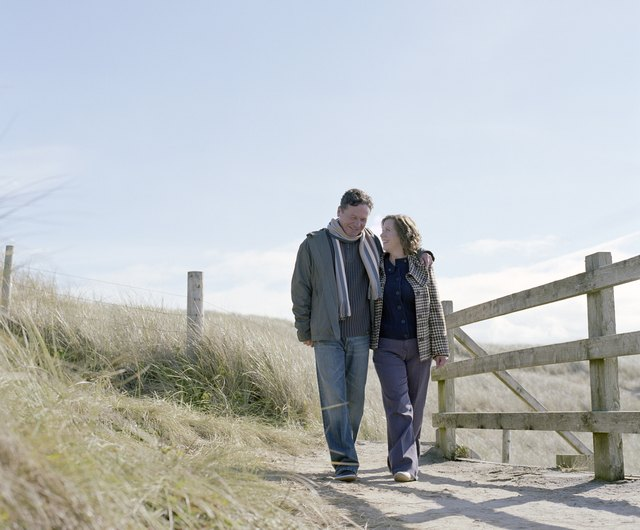 Mature couple walking on path by wooden rail, smiling