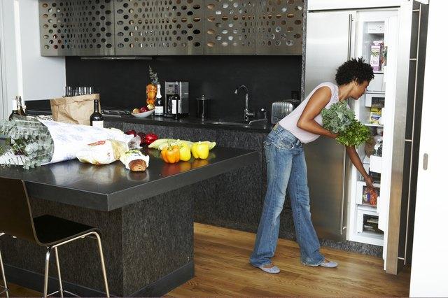 Woman Unpacking groceries in modern kitchen