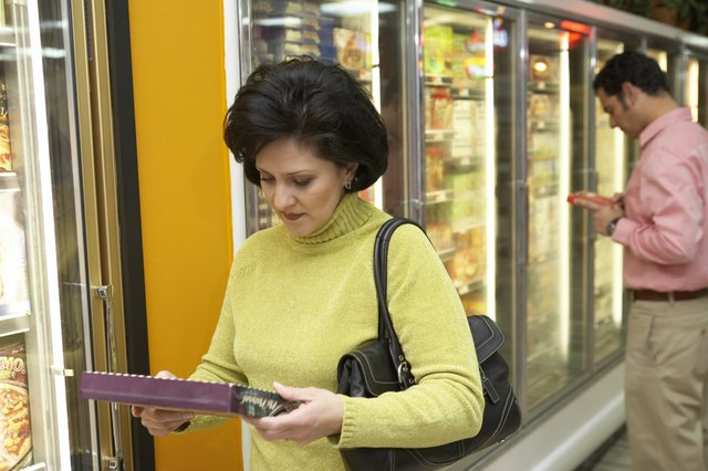 Mid adult woman holding a box of frozen desert in a supermarket