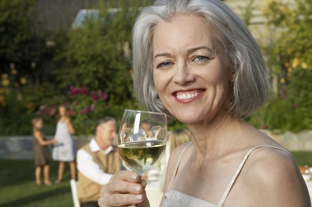 Mature woman in garden holding wine glass, smiling, portrait, close-up