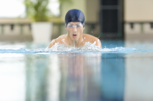 Man swimming in the pool, front view, defocused