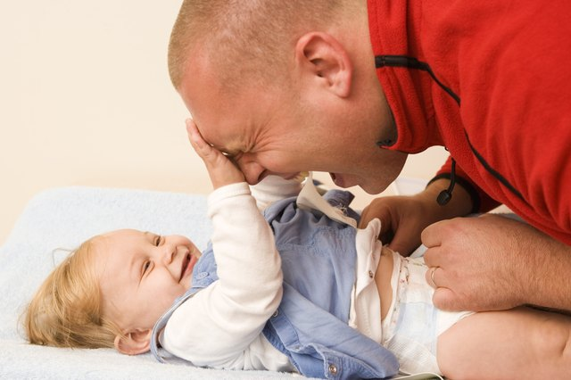 Baby playing with father as diaper is changed