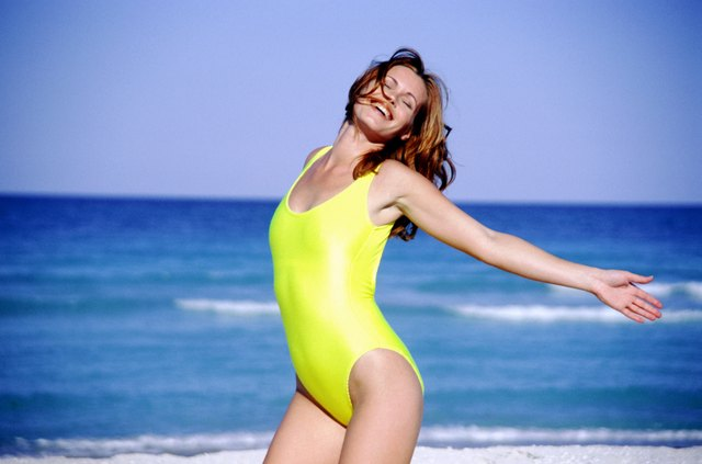 Young woman on beach with arms outstretched, smiling