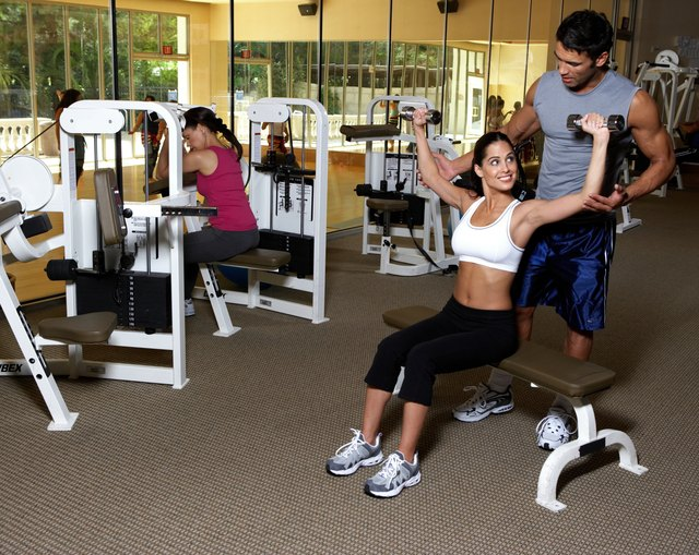 Male instructor giving weight training to woman in gym