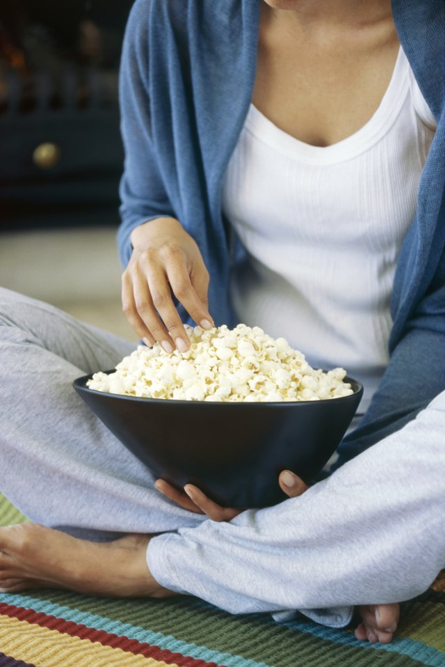 Mid section view of a young woman holding popcorns in a bowl
