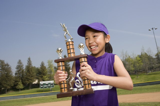 Little league player holding trophy