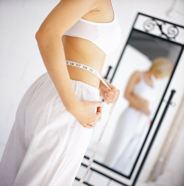 low angle side profile of a woman measuring her waist with an inch tape in the mirror