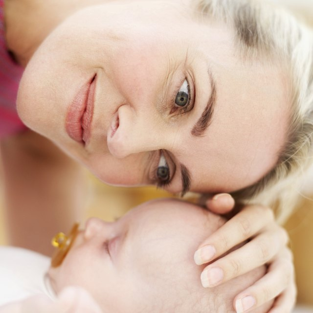 Close-up of a woman touching the top of a baby's head (3-6 months)