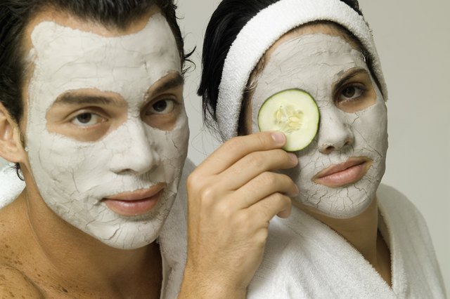A young couple with face packs and cucumber slice