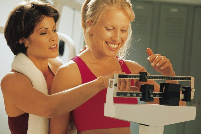 Woman standing on a scale as trainer helps weigh her