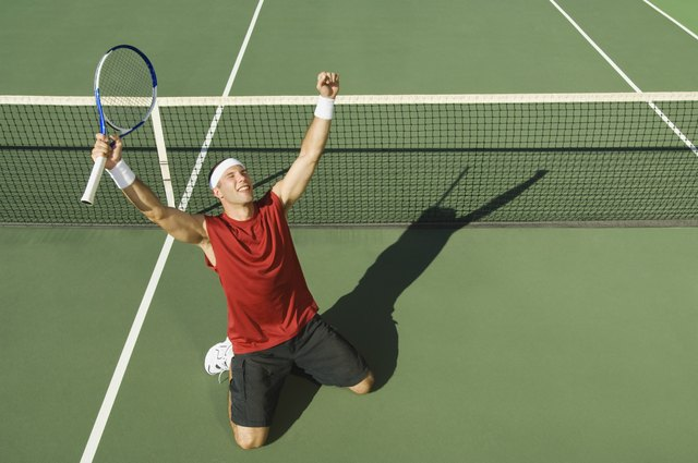 Victorious tennis player with arms outstretched