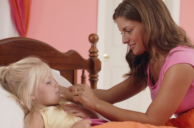 Mother taking daughter's temperature with thermometer
