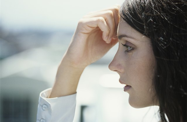 Young woman with hand on forehead outdoors,close-up,profile