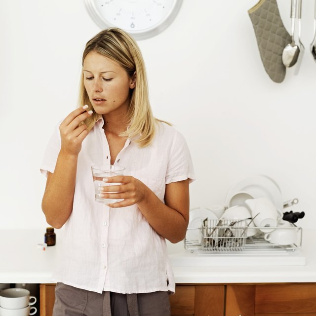 young woman holding a glass of water and a pill