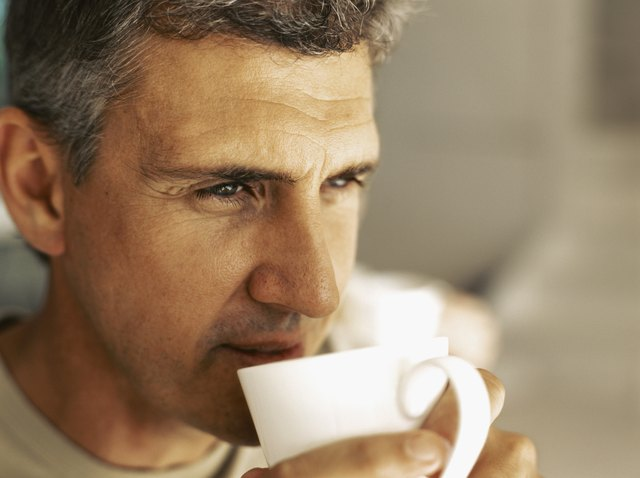 close-up of a mature man drinking a cup of tea