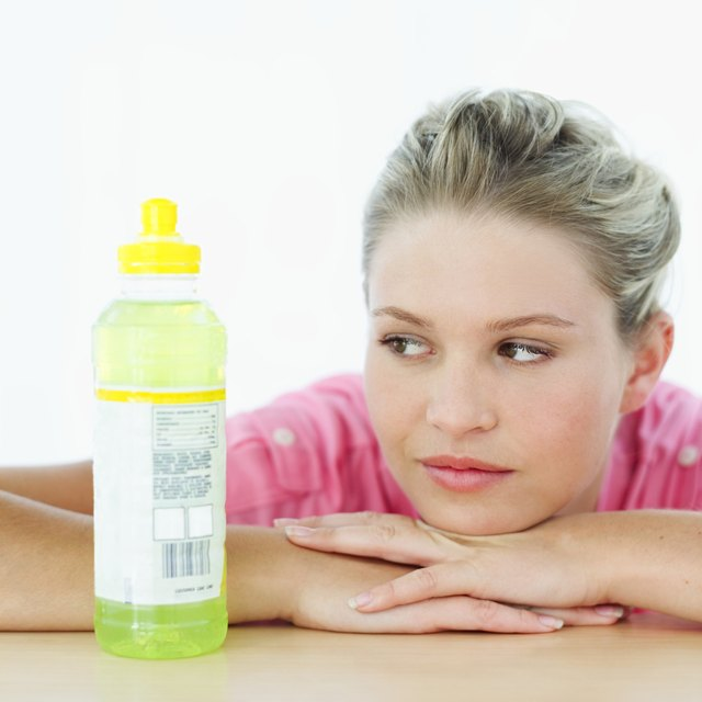 Young woman leaning on a table top looking at a bottle