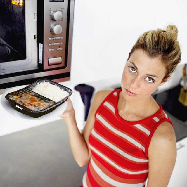 Young woman placing a microwave dinner in the microwave