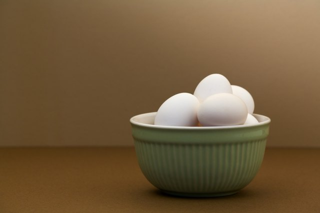White eggs in green bowl on brown table