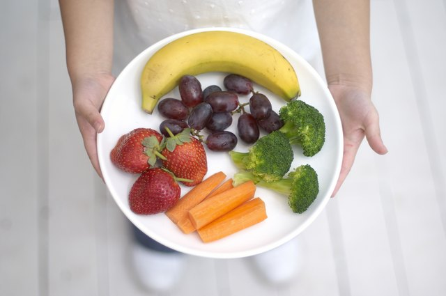 Girl holding plate of fruit and vegetables, including banana, strawberries, grapes, broccoli, carrots